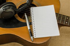 Blank paper with pen on old acoustic guitar Stock Photo