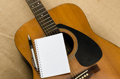 Blank paper with pen on old acoustic guitar Stock Photos
