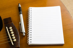 Blank paper with pen on old acoustic guitar Royalty Free Stock Images