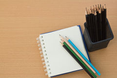 Blank paper and pencils. On old wooden table Royalty Free Stock Photography
