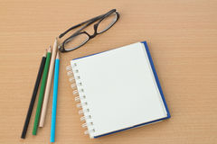 Blank paper and pencils. On old wooden table Royalty Free Stock Photo