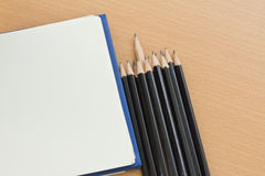 Blank paper and pencils. On old wooden table Stock Photos
