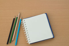 Blank paper and pencils. On old wooden table Stock Image