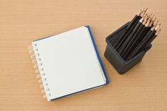 Blank paper and pencils. On old wooden table Stock Photography