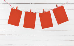 Blank paper or photo frames hanging on the red striped clothesline . Wooden background. Template for your text. Stock Image