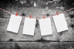 Blank paper or photo frames hanging on the red striped clothesline . Wooden background. Template for your text. Stock Images