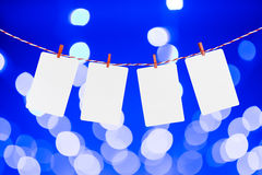 Blank paper or photo frames hanging on the red striped rope. Blurred defocused  blue color lights background, Template Stock Images