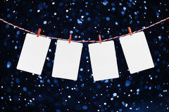 Blank paper or photo frames hanging on the red striped rope. Snowfall background, Template for your design. Royalty Free Stock Photo
