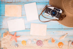 Blank paper photo frames with starfish, shells, coral and items on wooden table. Royalty Free Stock Photos