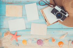 Blank paper photo frames with starfish, shells, coral and items on wooden table Stock Images