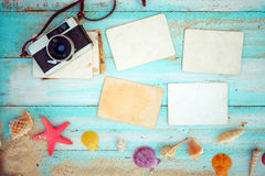 Blank paper photo frames with starfish, shells, coral and items on wooden. Top view composition - Blank paper photo frames with starfish, shells, coral and items royalty free stock photography