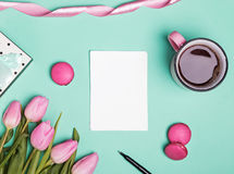 Blank paper, pink tulips, macarons and coffee in a mug Royalty Free Stock Photography