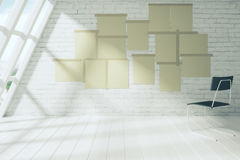 Blank paper posters on the brick wall of empty room with chair, Stock Image