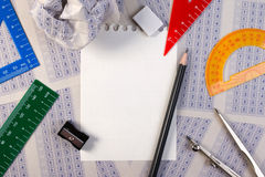 Blank paper reduction on vintage answer sheet with pencil, sharpener and drawing compasses. Stock Photos