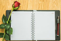 Blank paper and rose on wooden. View from above Royalty Free Stock Image