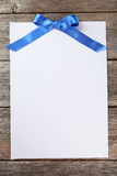 Blank paper sheet with blue bow on a grey wooden background Royalty Free Stock Image