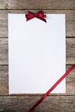Blank paper sheet with burgundy bow on the grey wooden background Royalty Free Stock Photography