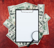 Blank paper sheet in clipboard placed on center of money dollar and wood background, business concept and information mockup Royalty Free Stock Photography