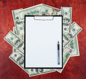 Blank paper sheet in clipboard placed on center of money dollar and wood background, business concept and information mockup Stock Images