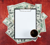 Blank paper sheet in clipboard placed on center of money dollar and wood background, coffee cup, business concept and information Royalty Free Stock Photo