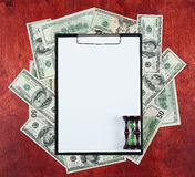 Blank paper sheet in clipboard placed on center of money dollar and wood background, sandglass, business concept and information m Stock Photography
