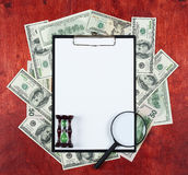 Blank paper sheet in clipboard placed on center of money dollar and wood background, sandglass and magnifier, business concept and Royalty Free Stock Photos