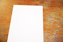 Blank paper sheet closeup. Close up of blank white paper sheet placed on aged wooden surface. Mock up, 3D Rendering Royalty Free Stock Image