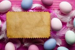 Blank paper sheet, colored Easter eggs and feathers stock photo