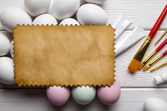 Blank paper sheet, colored and white eggs, brushes and paints on white table royalty free stock photo