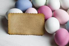 Blank paper sheet and colorful eggs on wooden table Royalty Free Stock Photos
