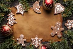 Paper sheet, gingerbread cookies, spruce tree and baubles royalty free stock photography
