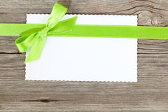 Blank paper sheet with green bow. On wooden background Royalty Free Stock Image