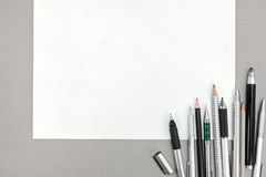 Blank paper sheet with pens and pencils on office table Stock Photo