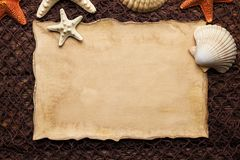 Blank paper sheet and shells on brown fishing net and wooden background stock images