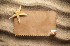 Blank paper sheet and shells on sand Stock Photos