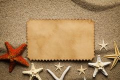Blank paper sheet and starfishes on the beach sand stock photo