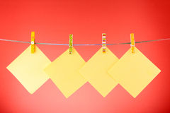 Blank paper sheets. On a clothes line against the red background Royalty Free Stock Photography