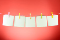 Blank paper sheets. On a clothes line against the red background Royalty Free Stock Photo