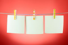 Blank paper sheets on a clothes line. Against the red background Royalty Free Stock Photos