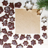 Blank paper surrounded by chocolate cookies. Empty square sheet of paper for recipes or congratulations, surrounded by chocolate cookies on white wooden table Stock Images
