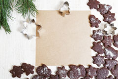 Blank paper surrounded by chocolate cookies. Blank sheet of paper for recipes or congratulations, surrounded by chocolate cookies on white wooden table. Top view Royalty Free Stock Images