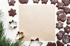 Blank paper surrounded by chocolate cookies. Blank sheet of paper for recipes or congratulations, surrounded by chocolate cookies on white wooden table. Top view Stock Photos