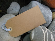 Blank paper tag on stones. Brown paper tag among pile of rocks Royalty Free Stock Photography