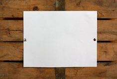 Blank paper on wooden wall. Piece of blank paper tacked to wooden background.Ready for your text Stock Photos