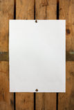 Blank paper on wooden wall. Piece of blank paper tacked to wooden background.Ready for your text Royalty Free Stock Photo