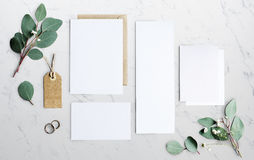Blank Papers Laying on Marble Table With Leaves Decoration Stock Photography