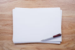Blank Papers and Pen with Crumpled Papers on Sides Stock Photo