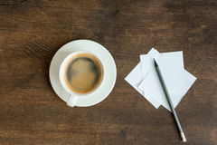 Blank papers with pencil and cup of coffee on wooden table top. Top view of blank papers with pencil and cup of coffee on wooden table top Stock Photo