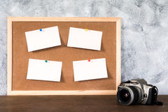 Blank papers pin up on cork board and camera over wooden table w Royalty Free Stock Photos