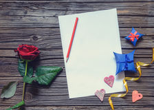 Blank papers on table with rose and gift Stock Image